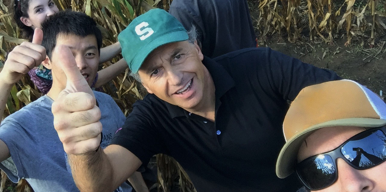 Bruno Basso with labmemebers giving thumbs up in corn field